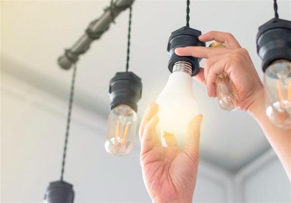 destaque para mãos fazendo troca de equipamento de iluminação