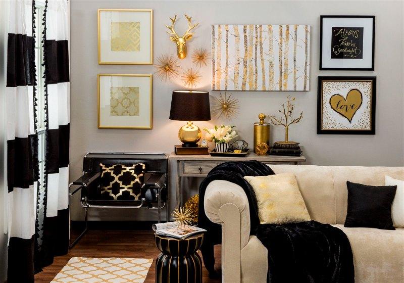 Imagem de uma sala contendo sofá, quadros e outros itens de decoração com a cor dourada e outros tons neutros