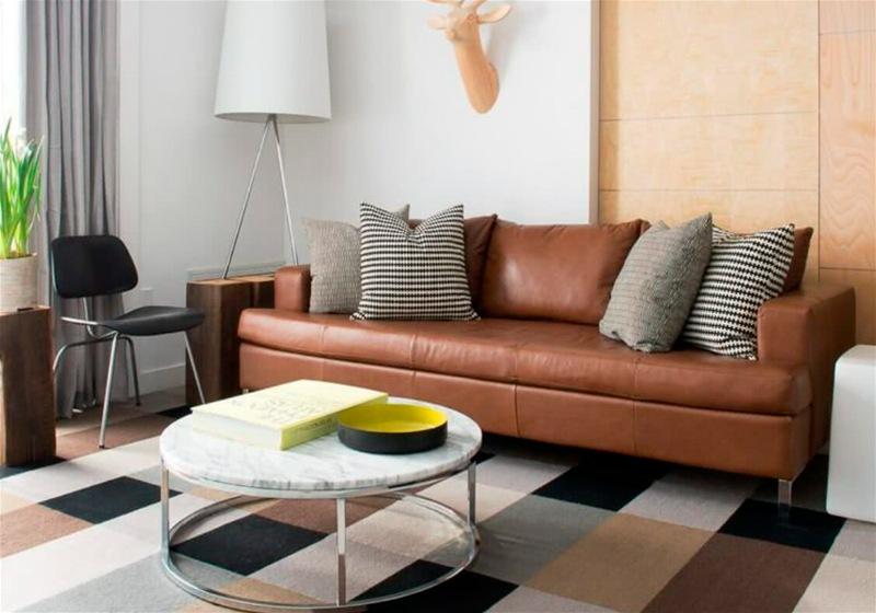 Imagem de uma sala de estar com sofá, almofadas listradas, mesa de centro e tapete