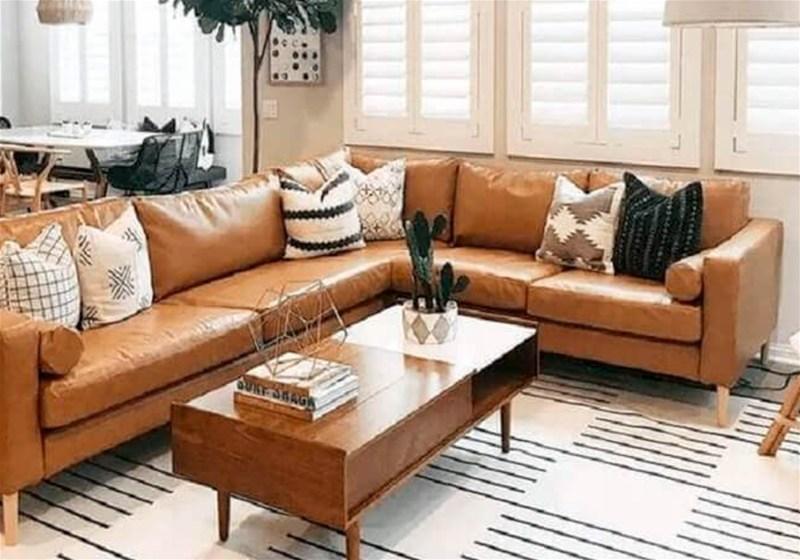 Imagem de uma sala de estar com sofá de couro, mesa de centro e tapete