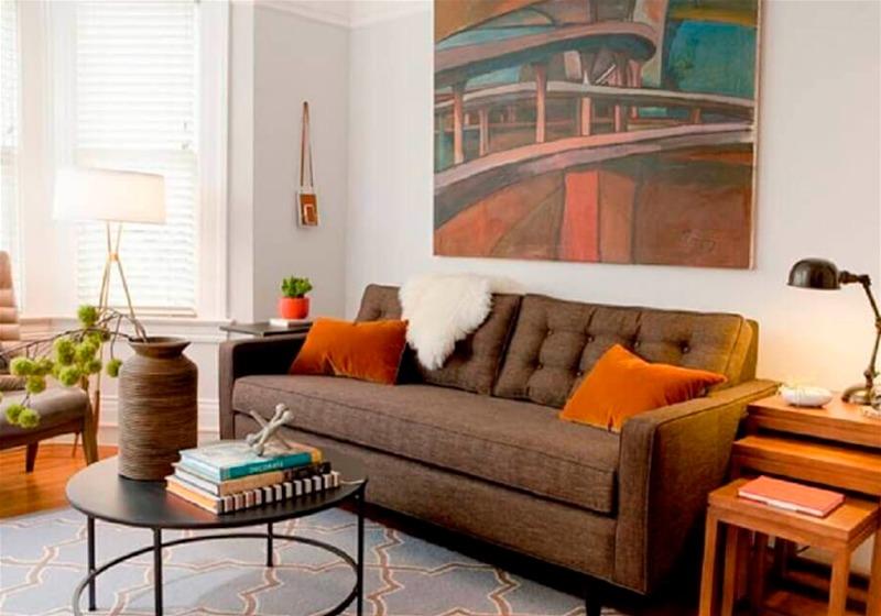 Imagem de uma sala de estar com sofá marrom, almofadas laranjas e ornamentos com tonalidades claras, como tapetes e mesa de cabeceira
