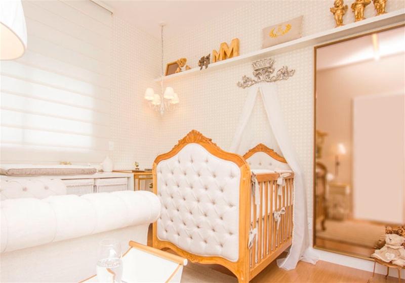 Imagem de um quarto de bebê com ornamentos dourados e brancos