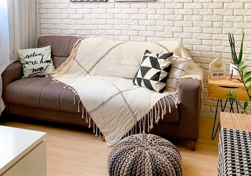 Imagem de uma sala de estar com sofá e uma manta