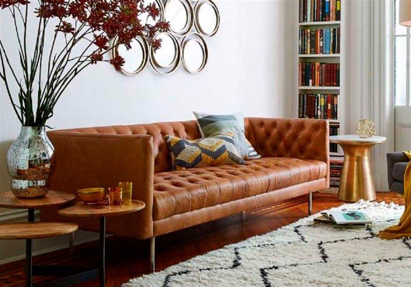Imagem de uma sala com sofá marrom e almofadas com estampas em formato zig zag