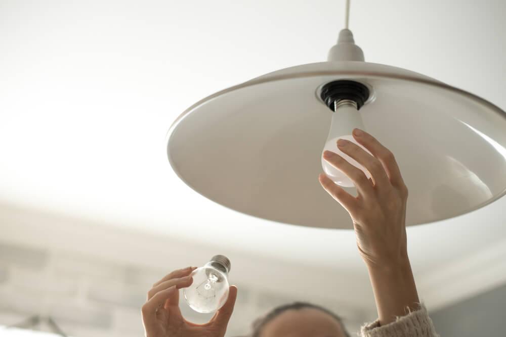 Imagem de uma pessoa trocando a lâmpada da casa para o tipo Bulbo