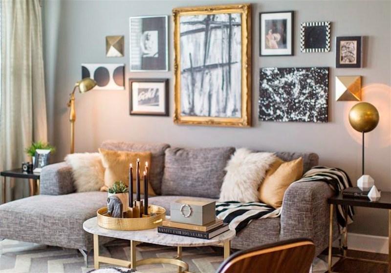 Imagem de uma sala de estar com sofá na cor cinza e objetos de decoração dourados