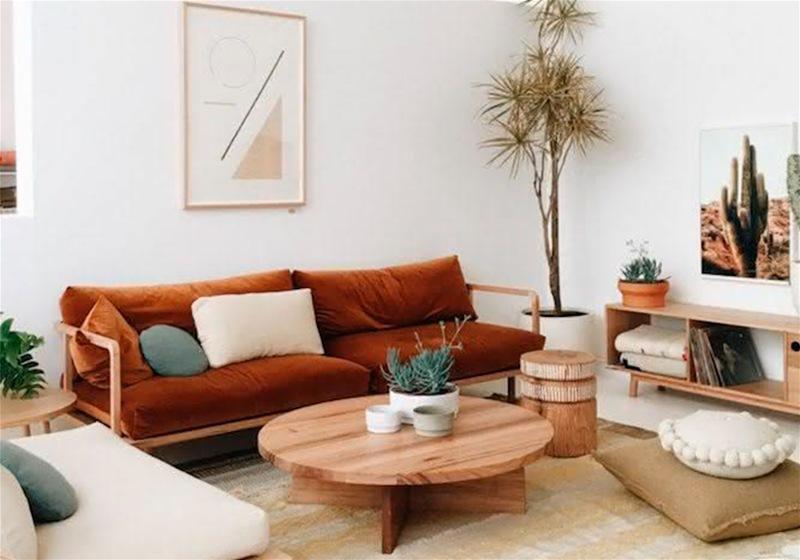 Imagem de uma sala decorada com sofá marrom, almofadas , quadro com cores neutras e mesa de centro