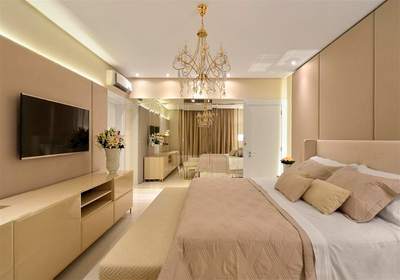 Imagem de uma sala de estar com a decoração que combina tons de dourado com bege