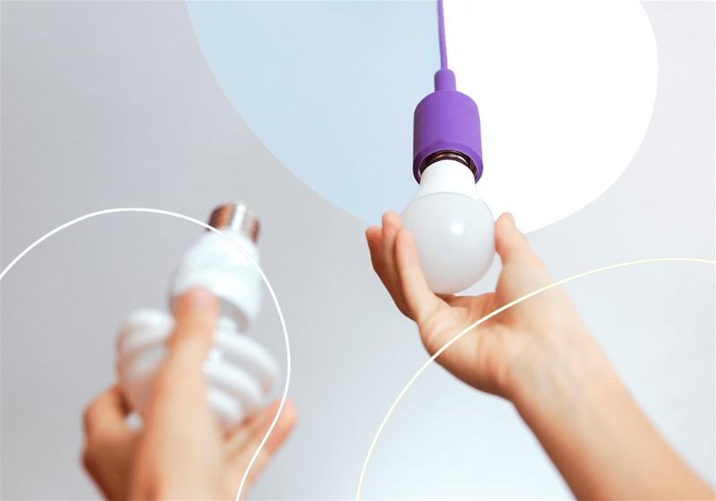Imagem em destaque de uma pessoa trocando a lâmpada de um ambiente interno