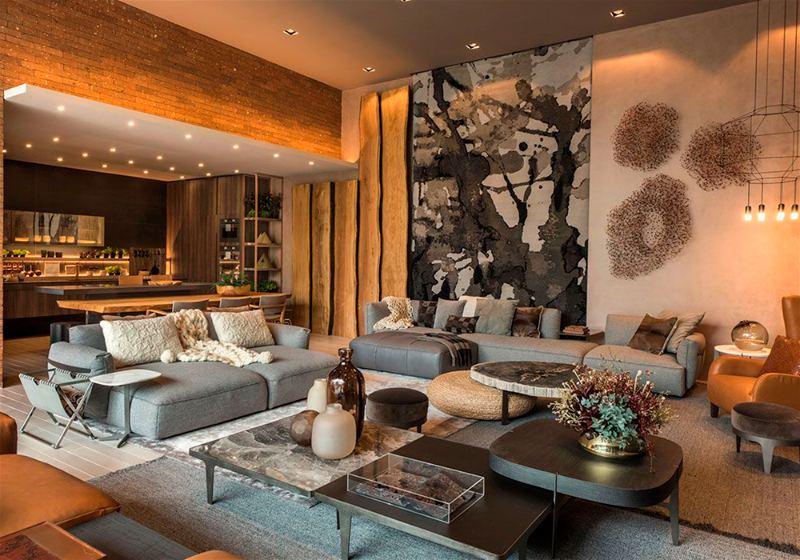 Imagem de uma sala de estar ampla, contendo vários móveis como sofás, mesas de centro, almofadas e itens de iluminação