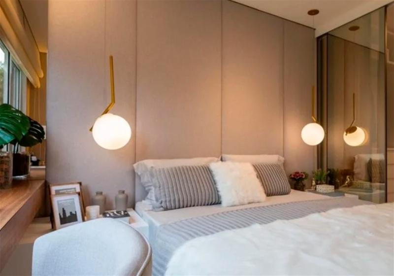 Imagem de um quarto de casal com cama, escrivaninhas e pendentes