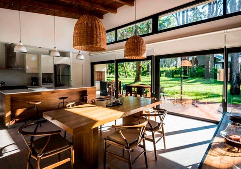 Imagem de uma cozinha de uma chácara, contendo mesa de centro, cadeiras de madeira, balcões e eletrodomésticos de cozinha