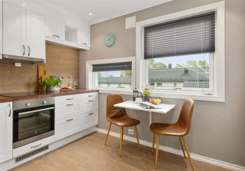 Imagem de uma cozinha compacta, contendo pia, mesa e duas cadeiras