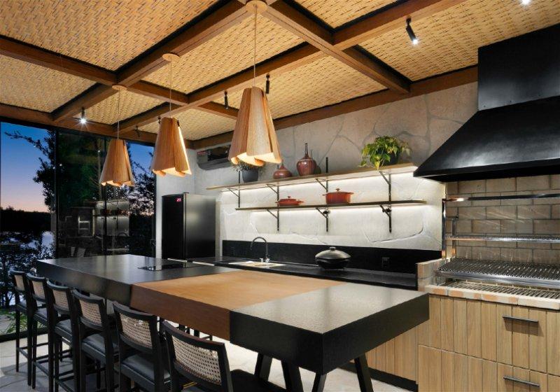 Imagem de uma cozinha gourmet, localizada na parte externa de uma casa
