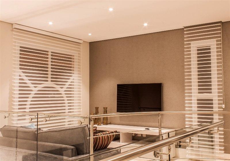 Imagem de sala de estar decorada com luminárias de tonalidades quentes e intimistas