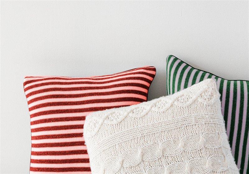 Imagem de 3 almofadas coloridas, nas cores vermelha, verde e branca