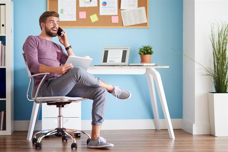 Imagem de um homem sentado em uma cadeira conversando no celular
