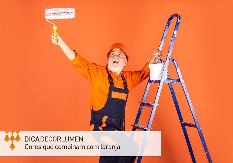 Imagem de um pintor em uma escada pintando uma parede de laranja